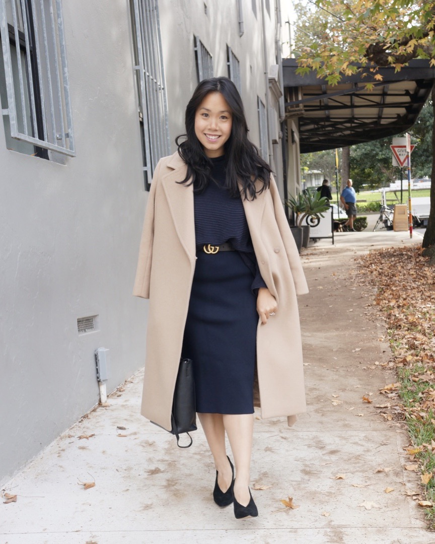 Woman wearing navy suit and camel coat with gucci belt