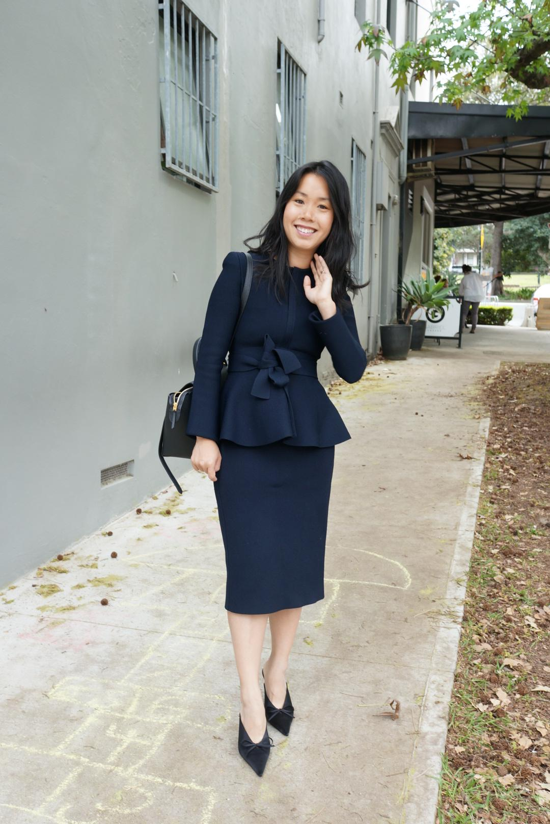Woman wearing navy suit with peplum jacket and pointy mules