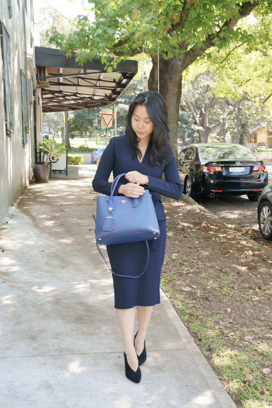Woman in navy suit carrying Prada Saffiano Double tote