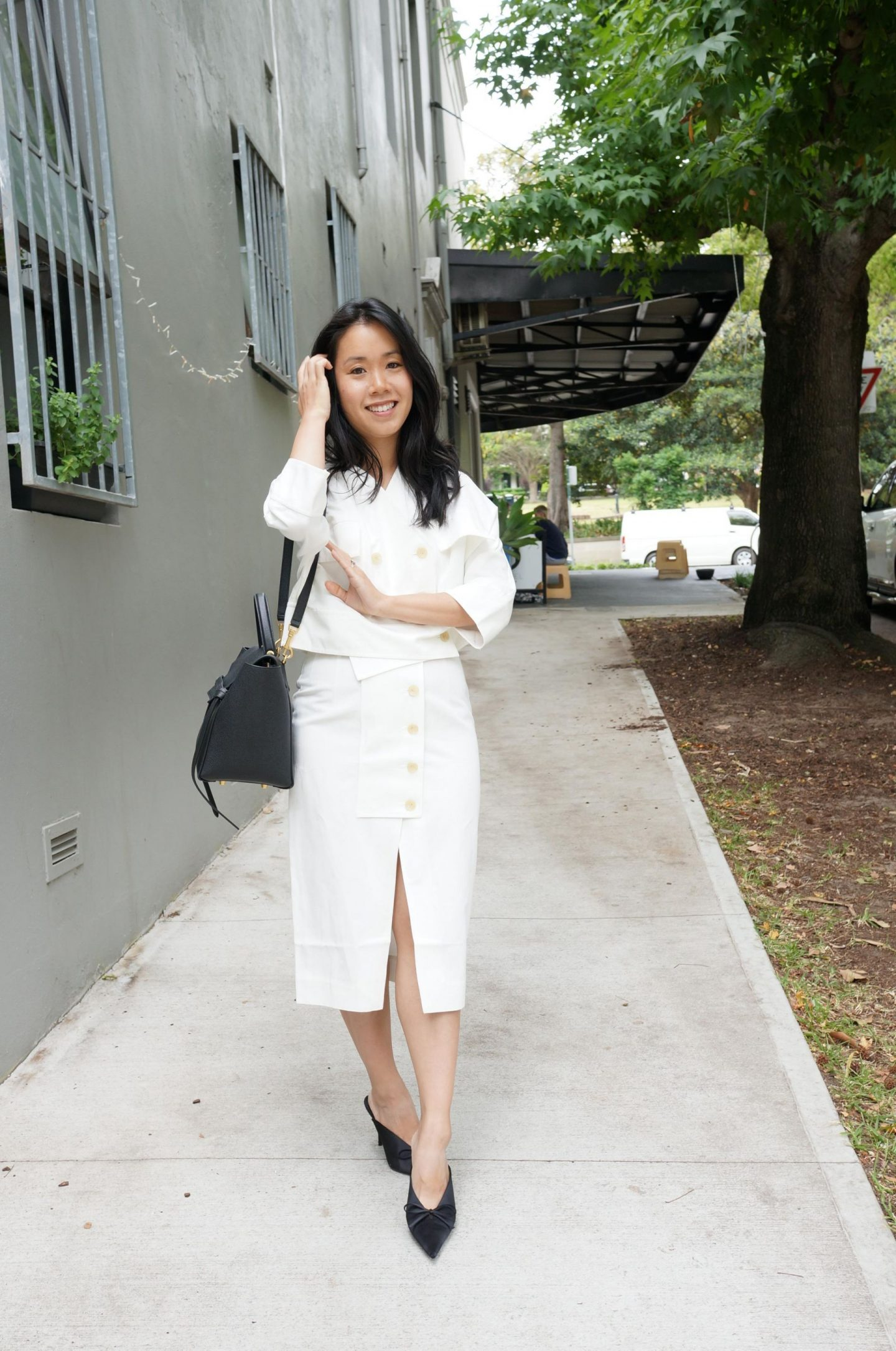 woman in oroton rtw white linen relaxed summer suit with black bag and black mules