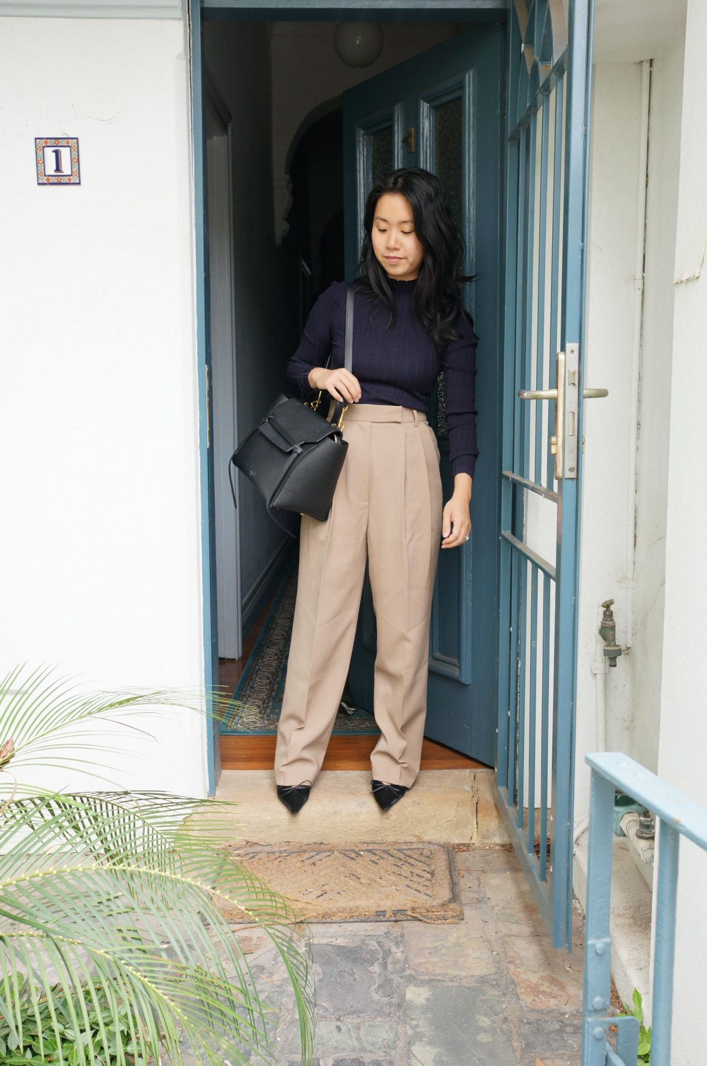 woman wearing the frankie shop wide leg beige trousers, navy top and black bag