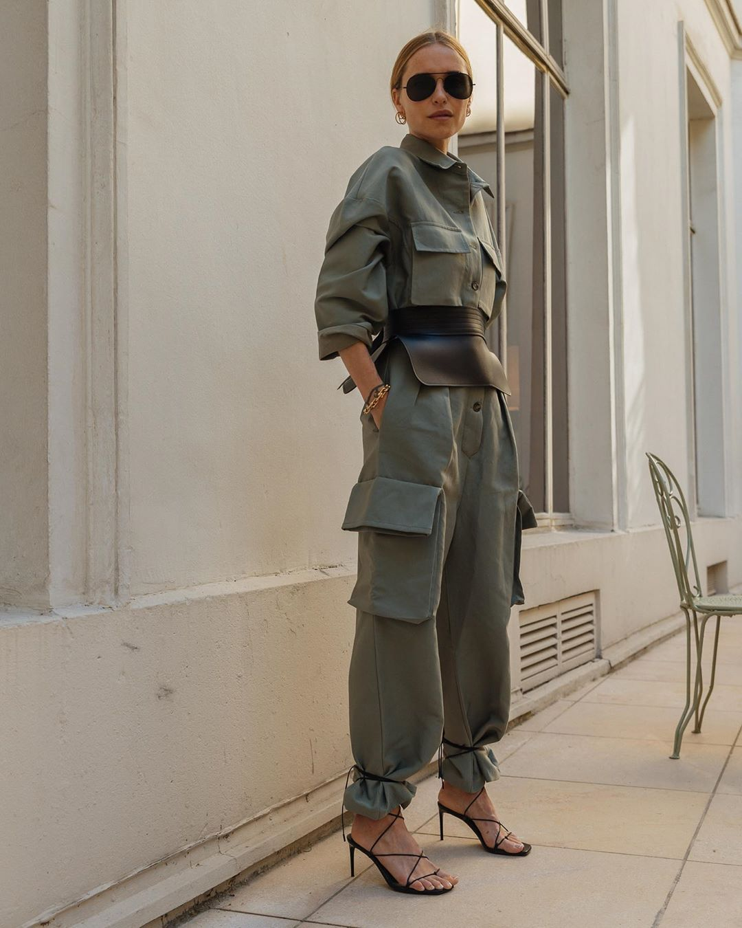 Woman fashion blogger wearing the frankie shop khaki jumpsuit with sunglasses and black strappy heels