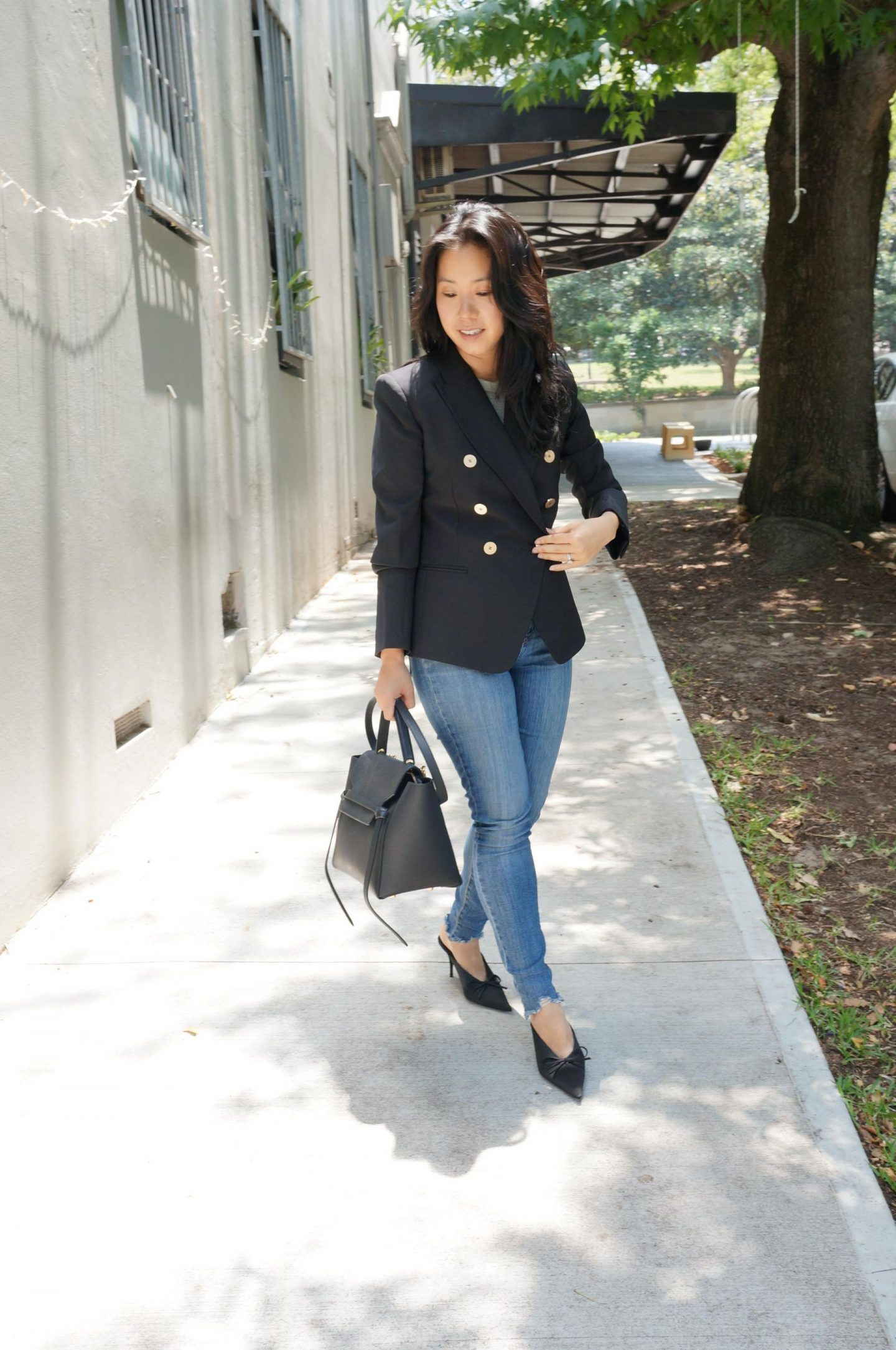 Woman wearing casual friday workwear to the office with black blazer, jeans and celine belt bag