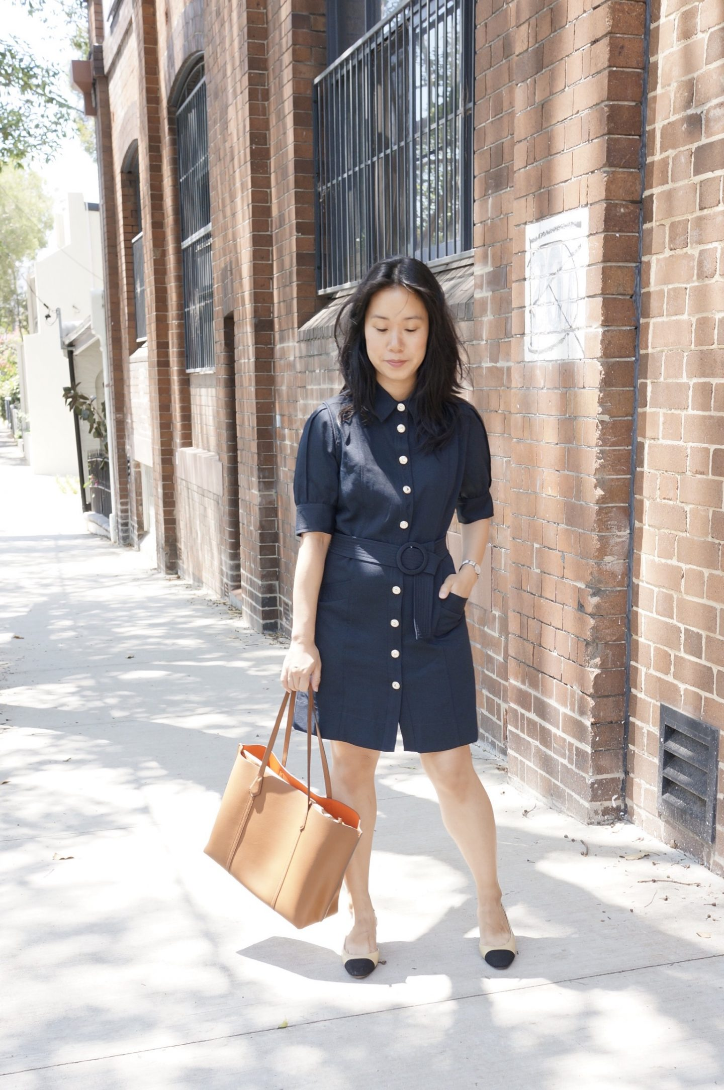 woman in navy shirt dress carrying tory burch perry tote and wearing chanel slingback sandals
