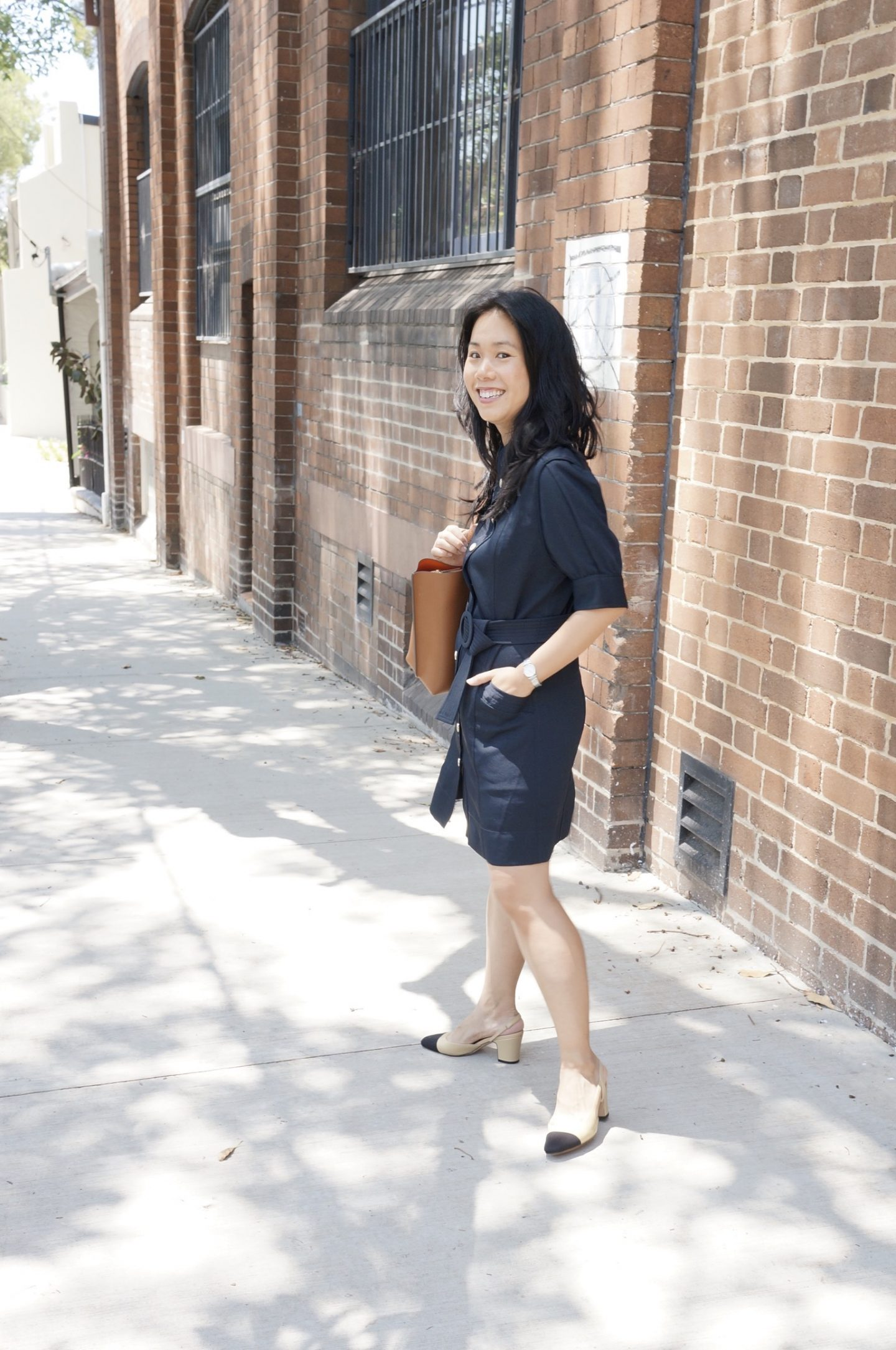 woman in navy shirt dress carrying camel bag and wearing chanel slingback sandals