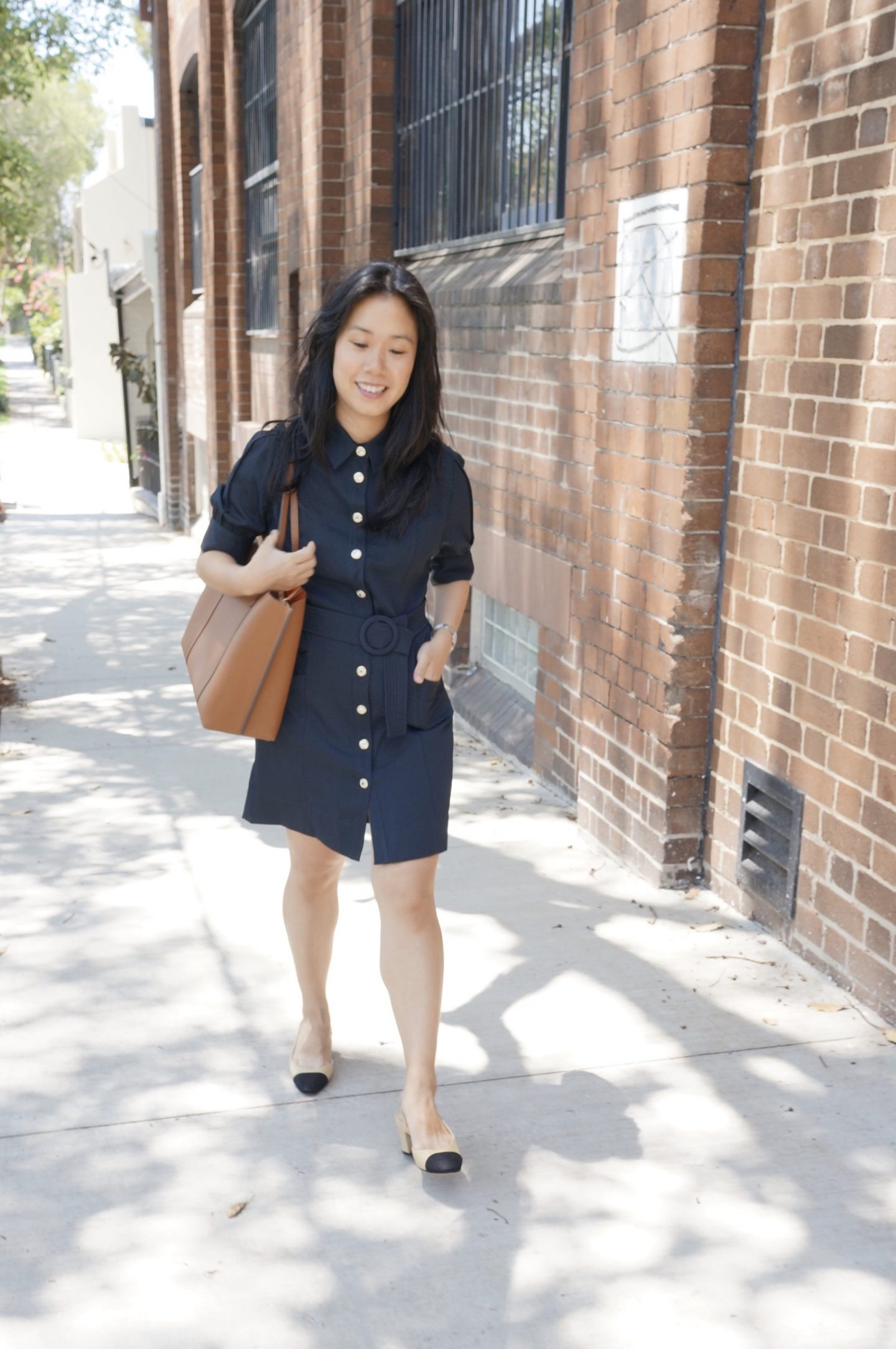 woman in navy shirt dress carrying camel tory burch perry tote bag and wearing chanel slingback sandals