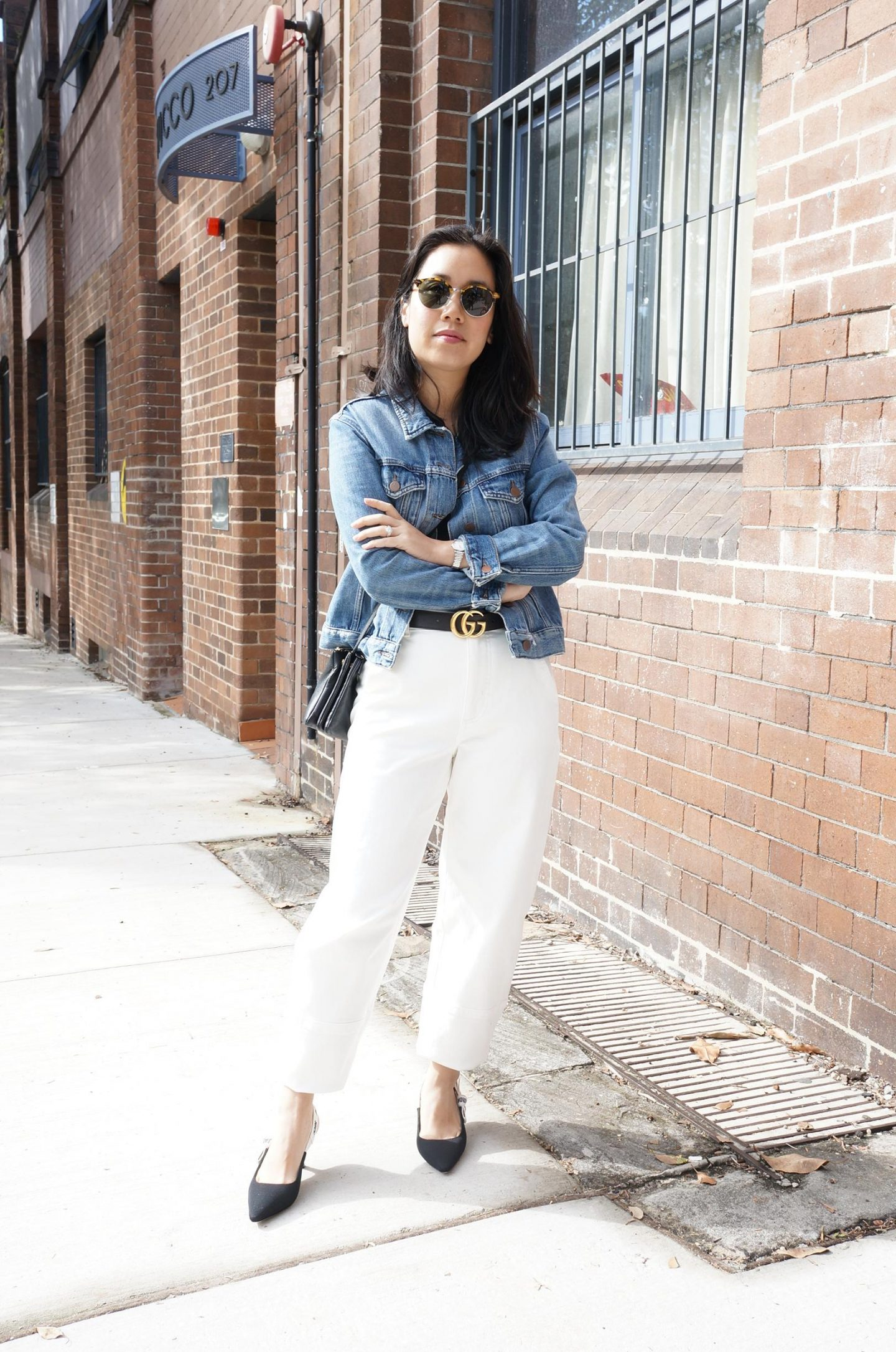 classic denim jacket styled with wide leg white jeans and gucci belt