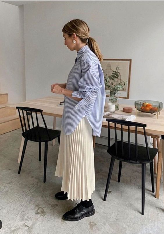 brittany bathgate wearing outfit with blue oversized shirt and pleated skirt