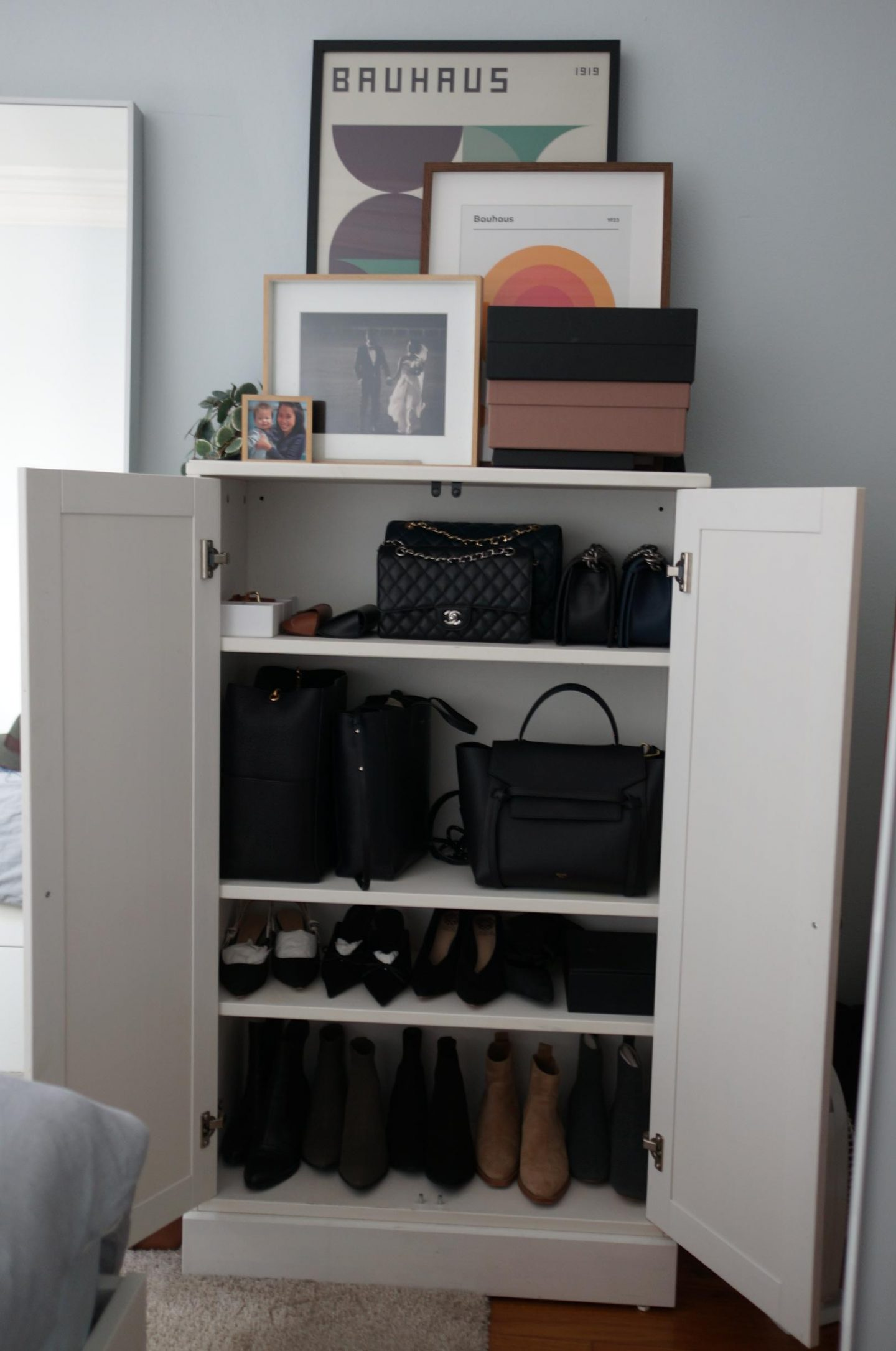open cupboard showing designer handbag collection in blog post about caring for your handbags so they last