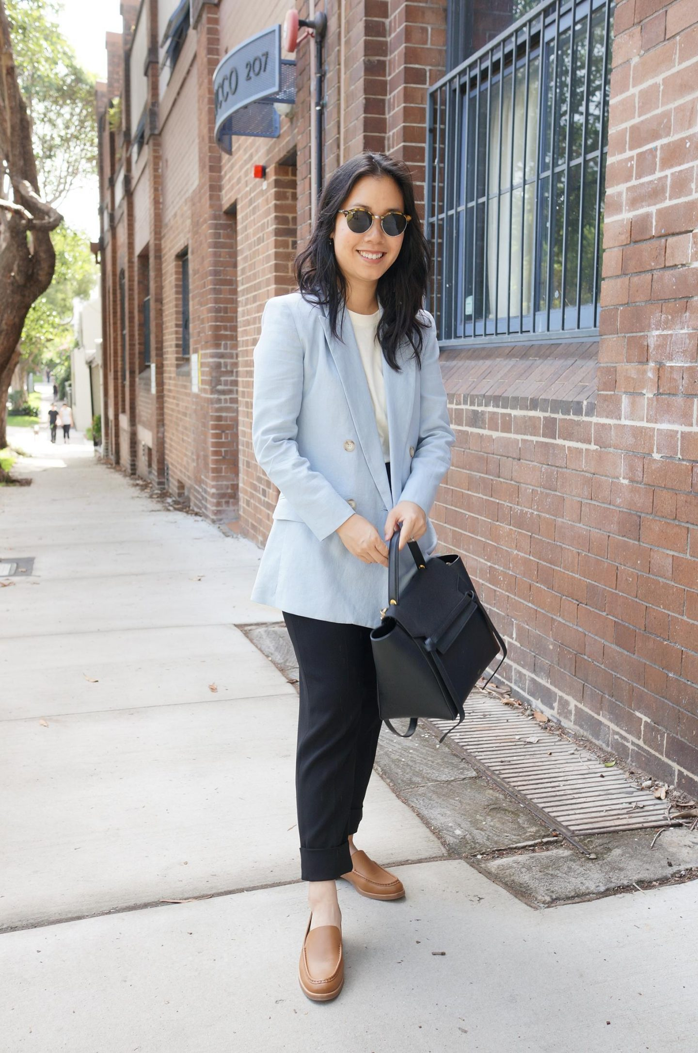 woman wearing light blue blazer and everlane modern loafers in camel featured in blog post about review