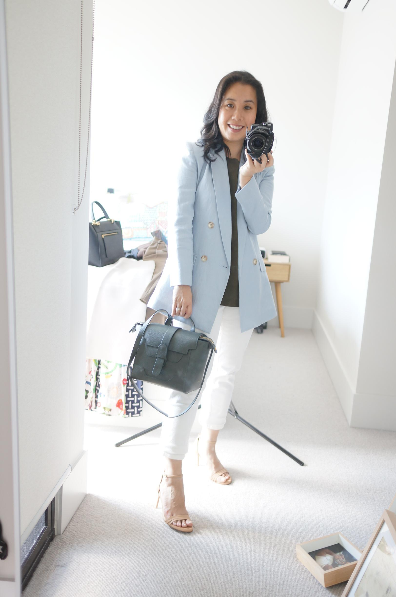 petite woman wearing blue blazer and white jeans in blog post sharing smart casual outfits
